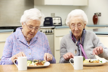 senior women enjoying a meal together in the kitchen