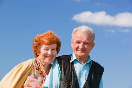 A happy elderly couple outside in a park during the summer months