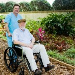 Nursing home orderly takes a senior man for a walk in the garden