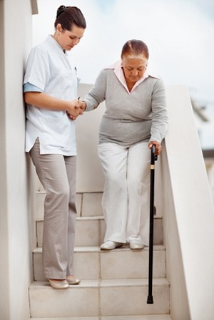 Young female nurse assisting an elderly woman to climb down the stairs