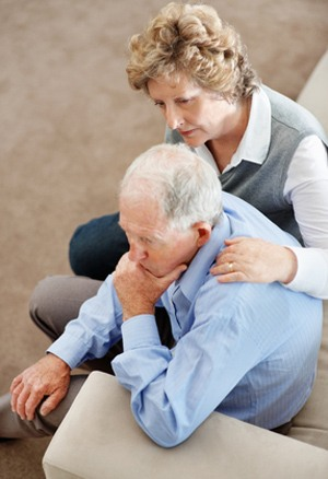Mother in a NYC hospital Portrait of a mature woman comforting senior man while sitting on sofa